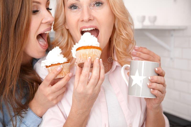 La madre y la hija juntas en casa weekend el primer que come las tortas fotografía de archivo