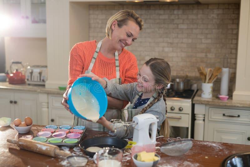 La madre y la hija que preparan la taza se apelmazan en cocina fotografía de archivo libre de regalías