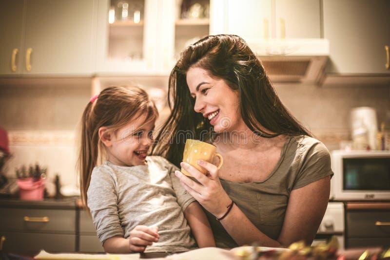 La madre y la hija se divierten en la cocina casera imagenes de archivo