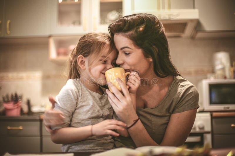 La madre y la hija se divierten junto La mamá me dejó intentar el café imagen de archivo