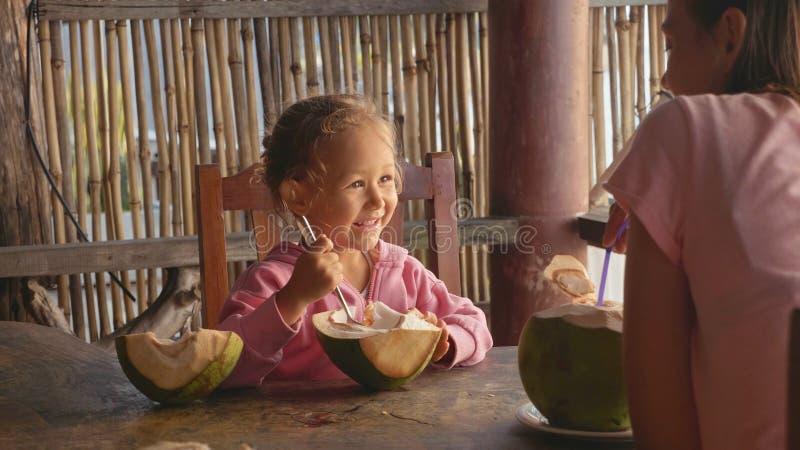 La madre y la hija se sienta en el café con los cocos fotografía de archivo libre de regalías