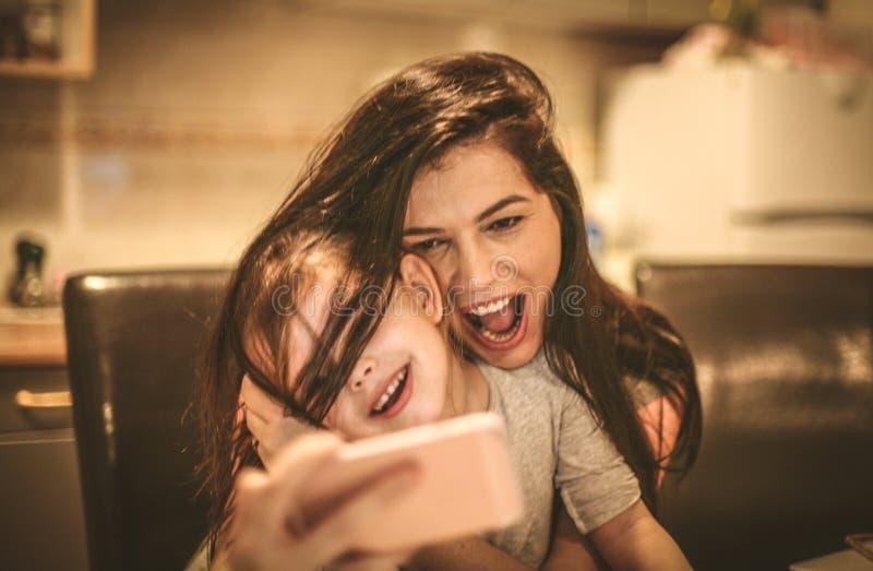 La madre y la hija toman el autorretrato con el teléfono elegante foto de archivo
