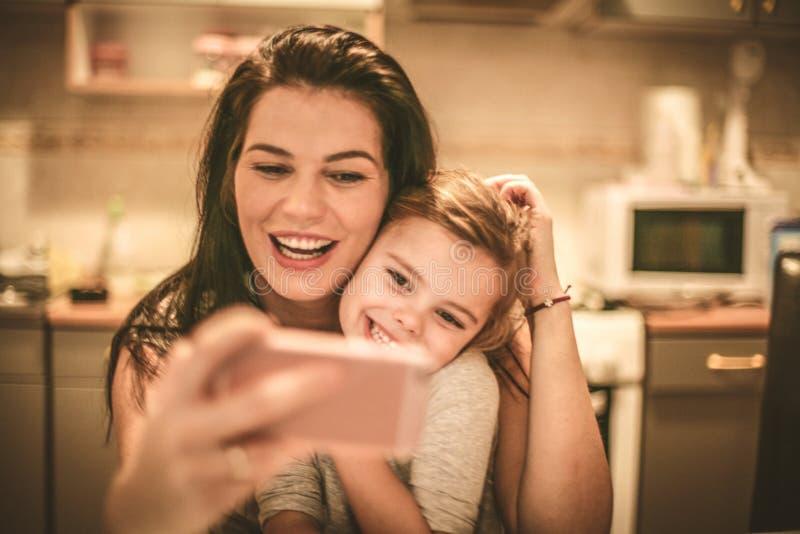 La madre y la hija toman un autorretrato usando el teléfono elegante fotos de archivo