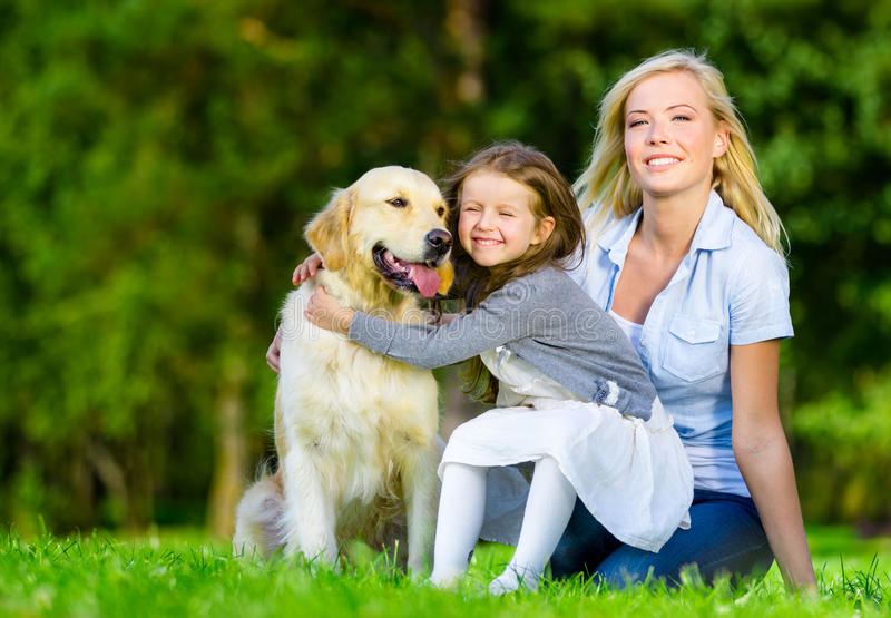 La madre y la hija con el animal doméstico están en la hierba verde fotografía de archivo