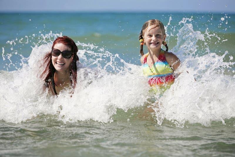 La madre y la hija disfrutan de día de verano caliente. foto de archivo