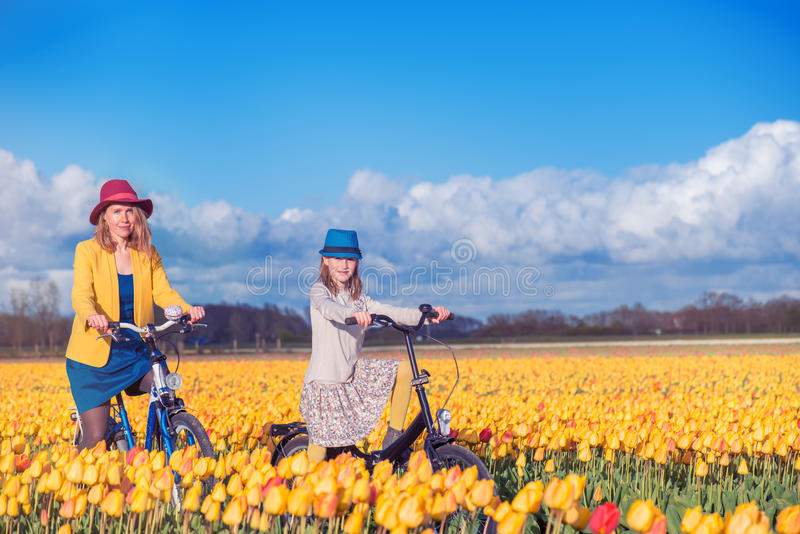 La madre y la hija en los tulipanes amarillos colocan fotografía de archivo libre de regalías