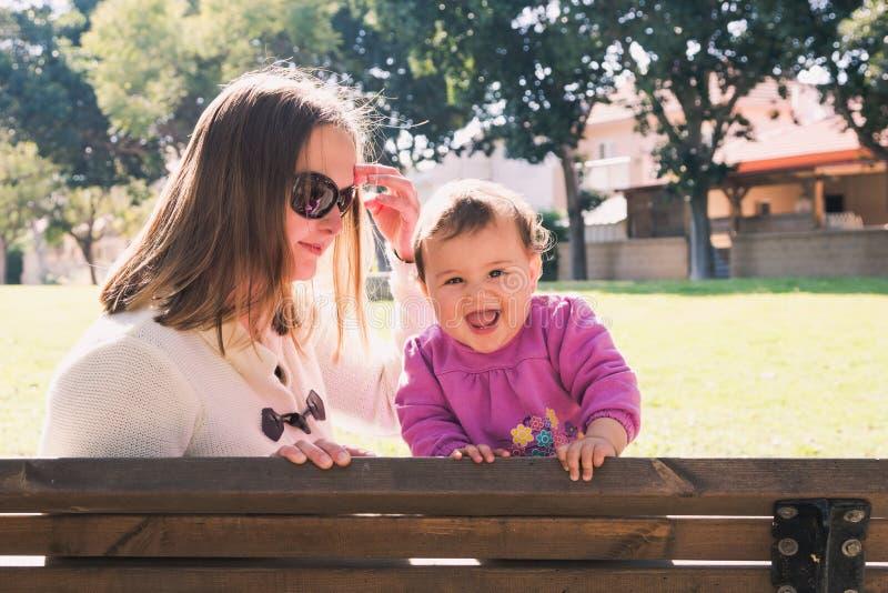 La madre y la hija felices están jugando en un parque fotos de archivo libres de regalías