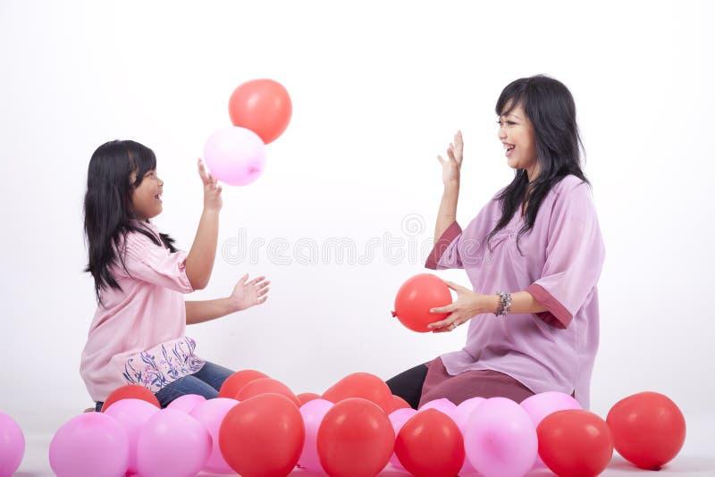 La madre y la hija felices juegan con el globo fotos de archivo