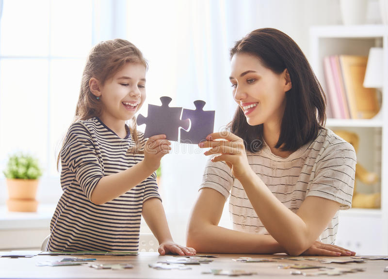 La madre y la hija hacen rompecabezas imagenes de archivo