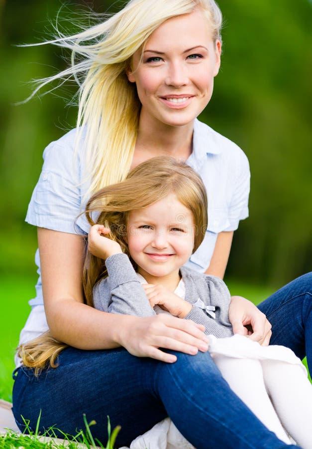 La madre y la hija se sientan en la hierba imágenes de archivo libres de regalías