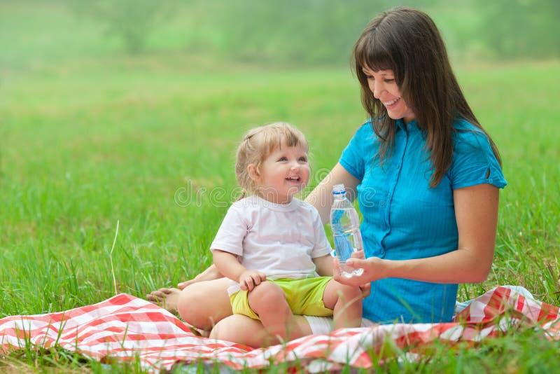 La madre y la hija tienen agua potable de la comida campestre imagen de archivo