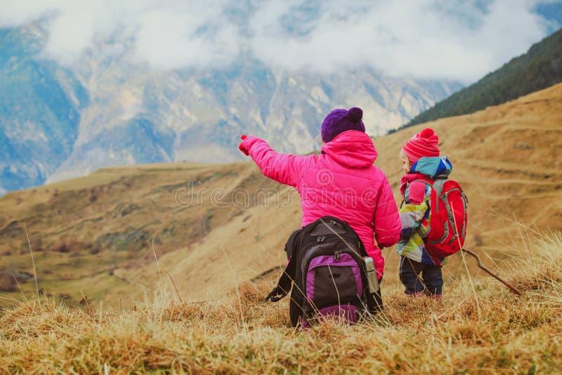 La madre y la pequeña hija viajan en montañas del invierno foto de archivo