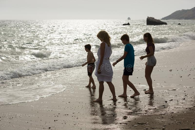La madre y los niños disfrutan de sus vacaciones en la playa arenosa y la agua de mar, última hora de la tarde en Chipre fotografía de archivo