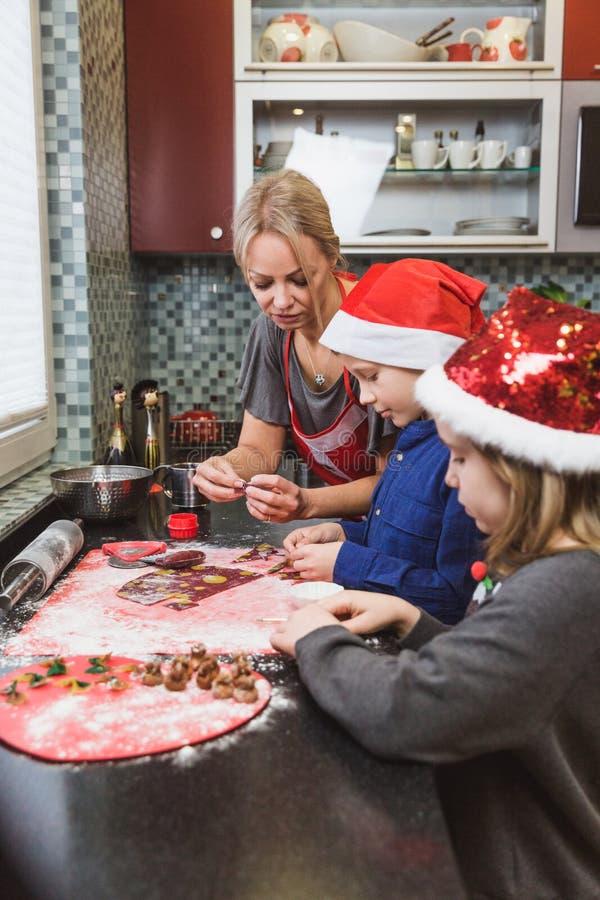 La madre y los niños felices hijo e hija de la familia cuecen las pastas para la Navidad imagenes de archivo