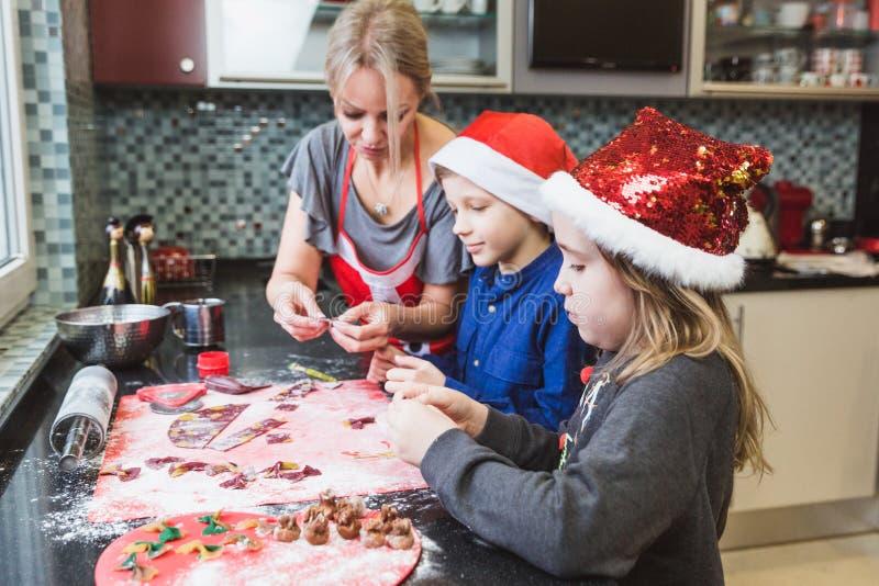 La madre y los niños felices hijo e hija de la familia cuecen las pastas para la Navidad imagen de archivo libre de regalías