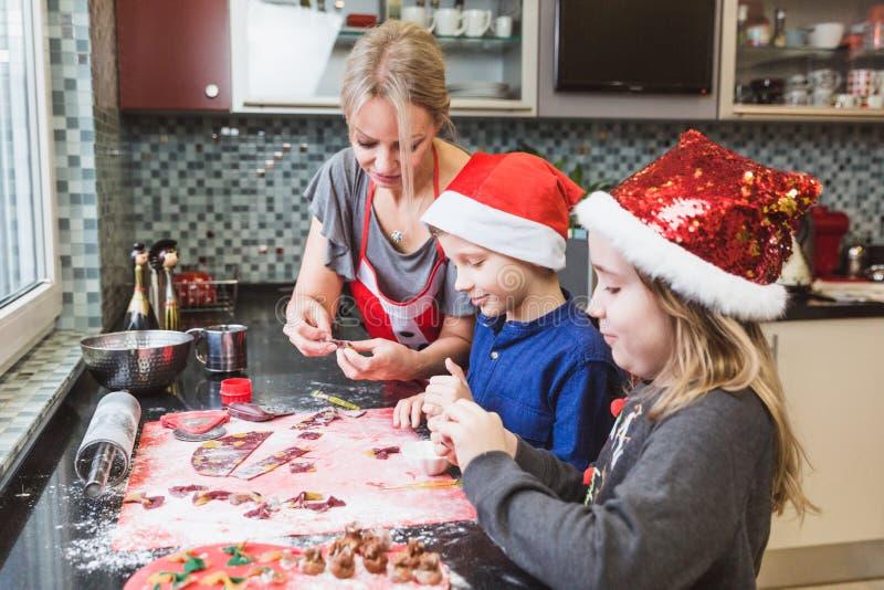 La madre y los niños felices hijo e hija de la familia cuecen las pastas para la Navidad fotografía de archivo libre de regalías