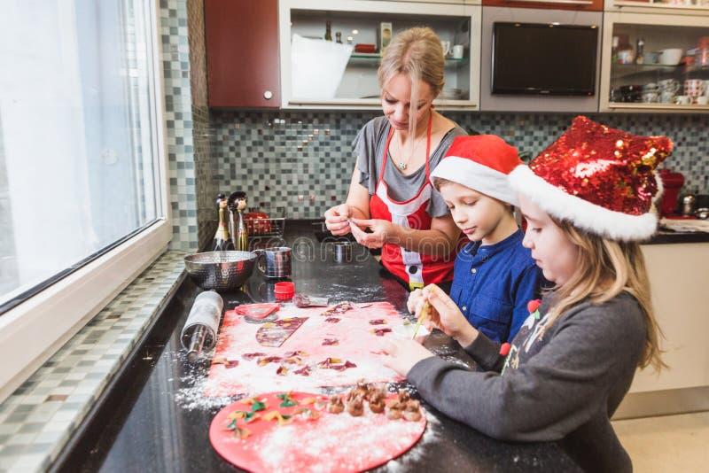 La madre y los niños felices hijo e hija de la familia cuecen las pastas para la Navidad imagen de archivo