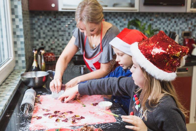 La madre y los niños felices hijo e hija de la familia cuecen las pastas para la Navidad fotos de archivo libres de regalías