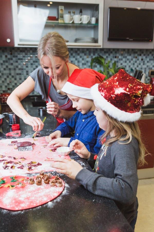 La madre y los niños felices hijo e hija de la familia cuecen las pastas para la Navidad foto de archivo