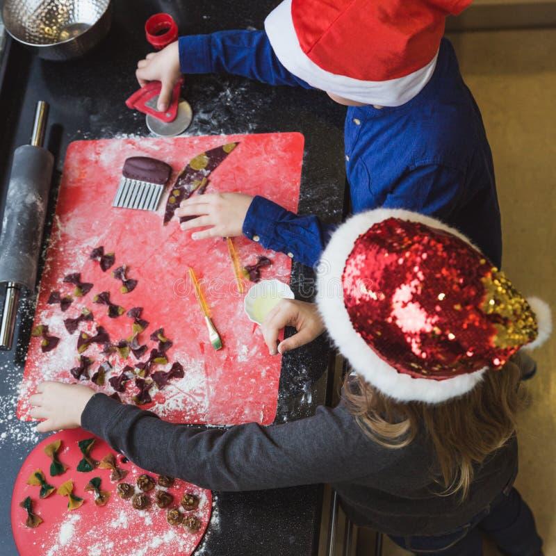 La madre y los niños felices hijo e hija de la familia cuecen las pastas para la Navidad imágenes de archivo libres de regalías