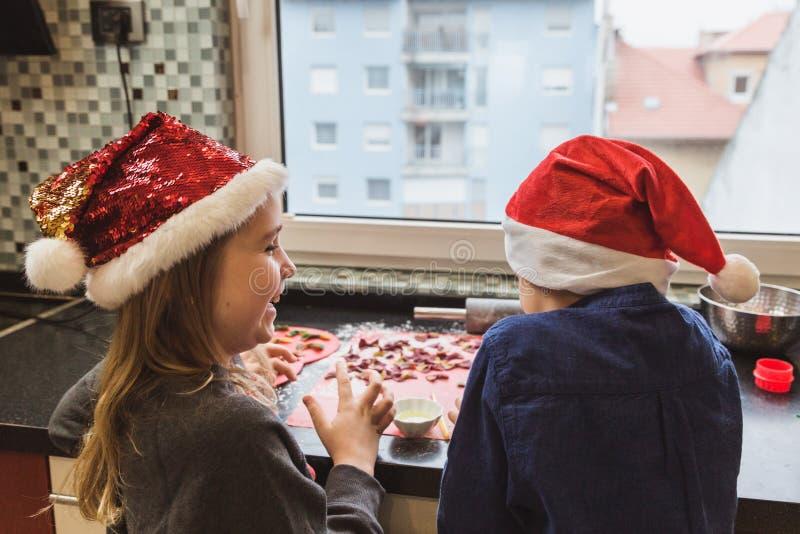 La madre y los niños felices hijo e hija de la familia cuecen las pastas para la Navidad foto de archivo libre de regalías