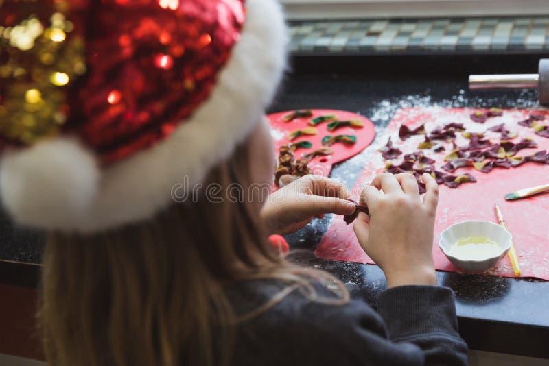La madre y los niños felices hijo e hija de la familia cuecen las pastas para la Navidad fotografía de archivo