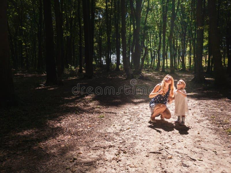 La madre y la niña en el sol se encienden dentro del bosque fotografía de archivo libre de regalías