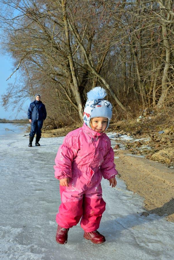 La madre y la niña jovenes en el sol se encienden en el hielo del río foto de archivo libre de regalías