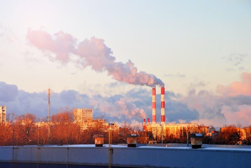 La madrugada con abajo asolea la luz, una vista al paisaje industrial de la ciudad con las emisiones de humo de las chimeneas fotos de archivo