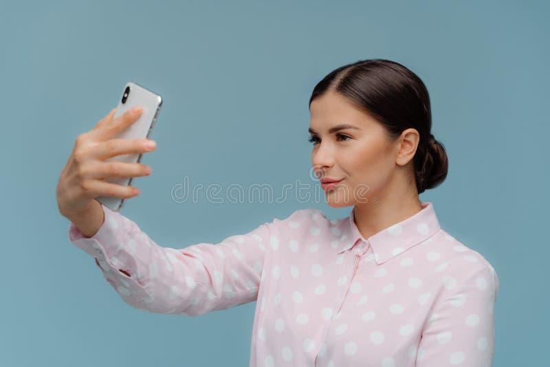 La maestra elegante atractiva con el pelo oscuro, estira la mano con celular moderno, hace el retrato del selfie, lleva polca ele fotos de archivo