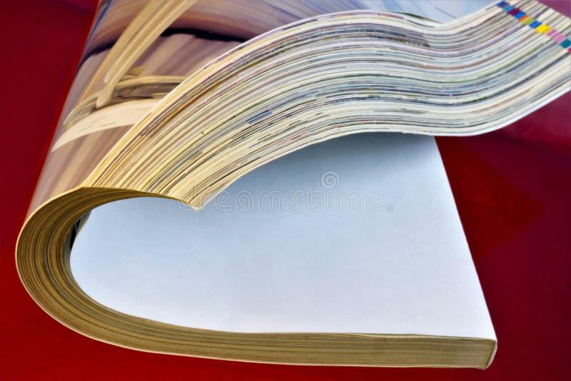 La magazine est un périodique imprimé de papier, sur un fond créatif rouge Le journal a un rubrication permanent et le contient photographie stock