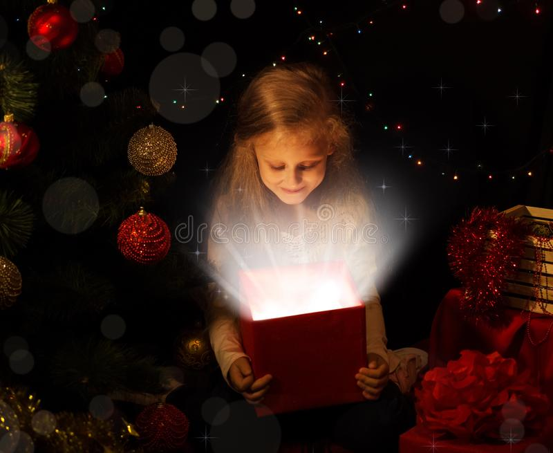La magia di natale La bambina apre un regalo magico sull'albero di Natale fotografia stock