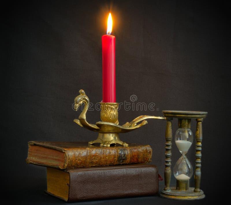 La magia prenota la clessidra e la candela fotografie stock