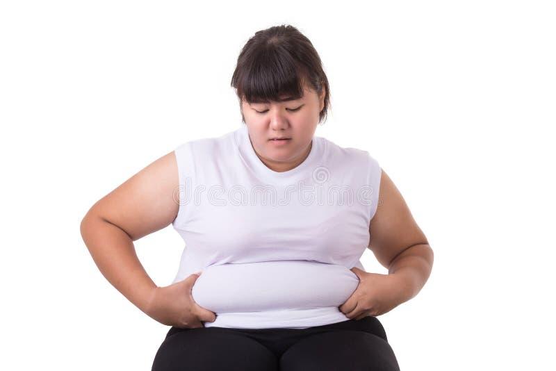 La maglietta bianca asiatica grassa di usura di donna si è preoccupata per la sua dimensione corporea fotografia stock libera da diritti