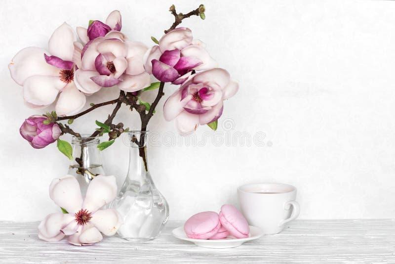 La magnolia rosada florece el ramo con la taza de café y macarons en el fondo de madera blanco fotos de archivo libres de regalías