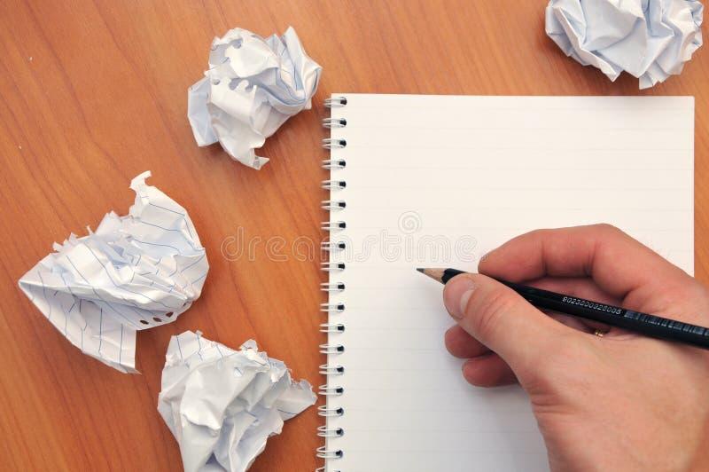 La main écrit dans un carnet autour d'un papier chiffonné photographie stock libre de droits