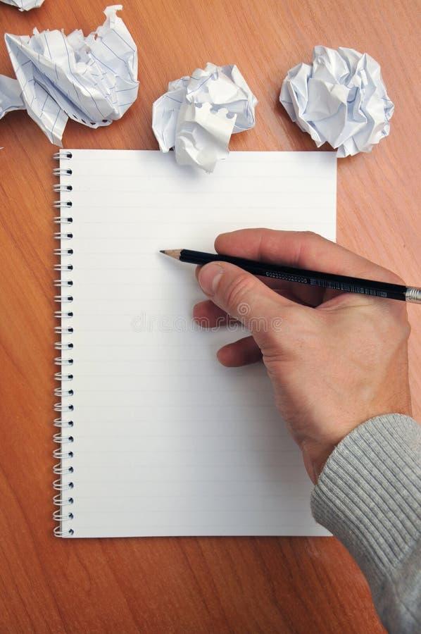 La main écrit dans un carnet autour d'un papier chiffonné images libres de droits