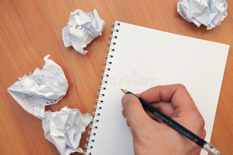 La main écrit dans un carnet autour d'un papier chiffonné photos libres de droits