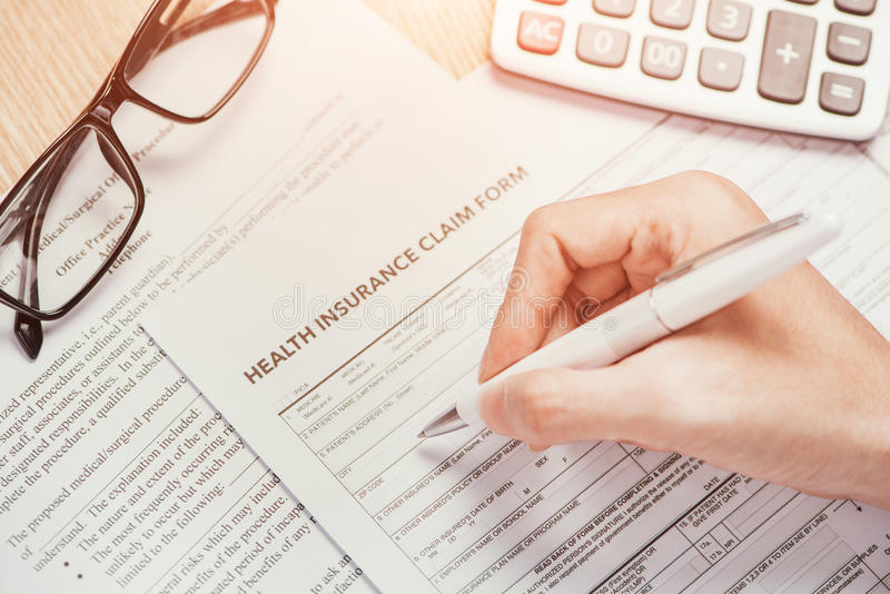 La main écrit l'information personnelle sur le formulaire de réclamation d'assurance médicale maladie images stock