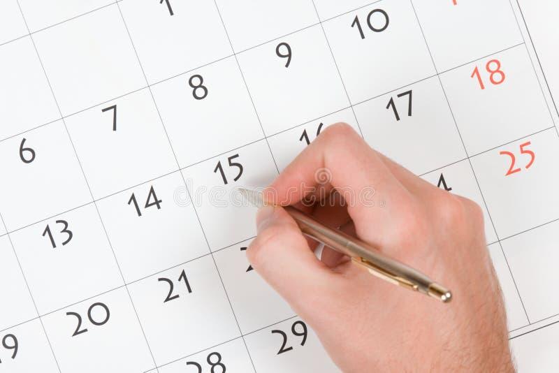 La main écrivent dans le calendrier image libre de droits