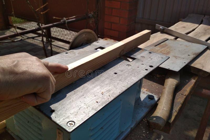 La main ancienne mâle tient une planche et traite le bord sur une machine universelle à broyer le bois de menuiserie dans la cour photo libre de droits