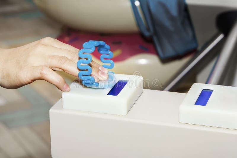 La main applique le bracelet au tourniquet pour le passage par le système de billet photo libre de droits