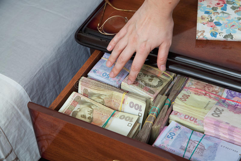 La main atteint pour l'argent dans la table de chevet photo stock