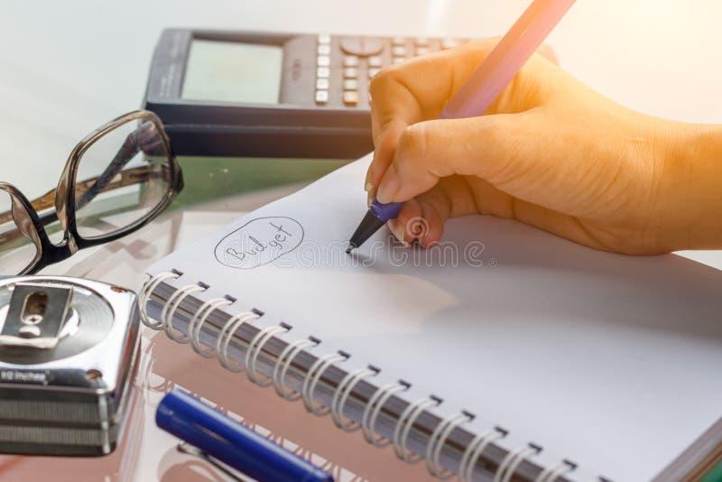 La main avec l'écriture de stylo sur le carnet et le fonctionnement calculent images stock