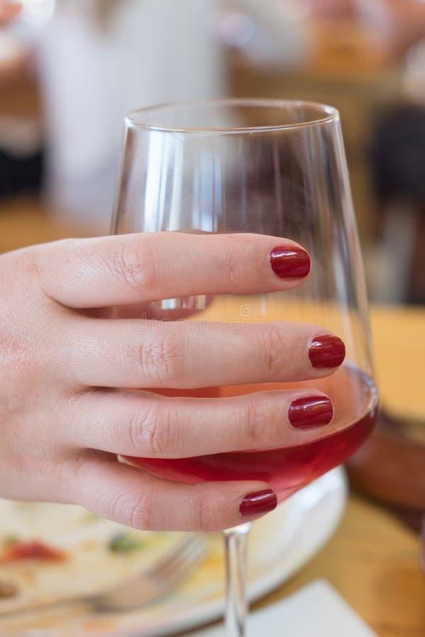 La main avec l'ongle de Bourgogne a poli des doigts tenant un verre de rouge photographie stock