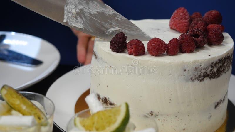 La main avec le couteau coupe la fraise Baies sur le conseil à cuire blanc Ingrédients frais pour un dessert Chef travaillant dan photos stock