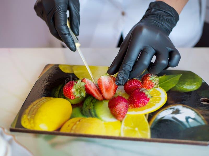 La main avec le couteau coupe la fraise Baies sur faire cuire le conseil Ingrédients frais pour un dessert Chef travaillant dans  photos libres de droits