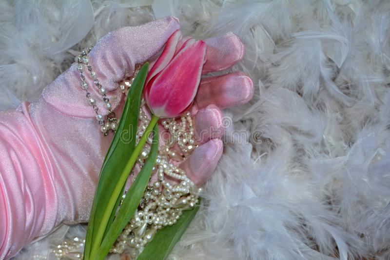 La main avec le gant tient la tulipe et la chaîne de perle, se trouve sur les plumes blanches photos stock