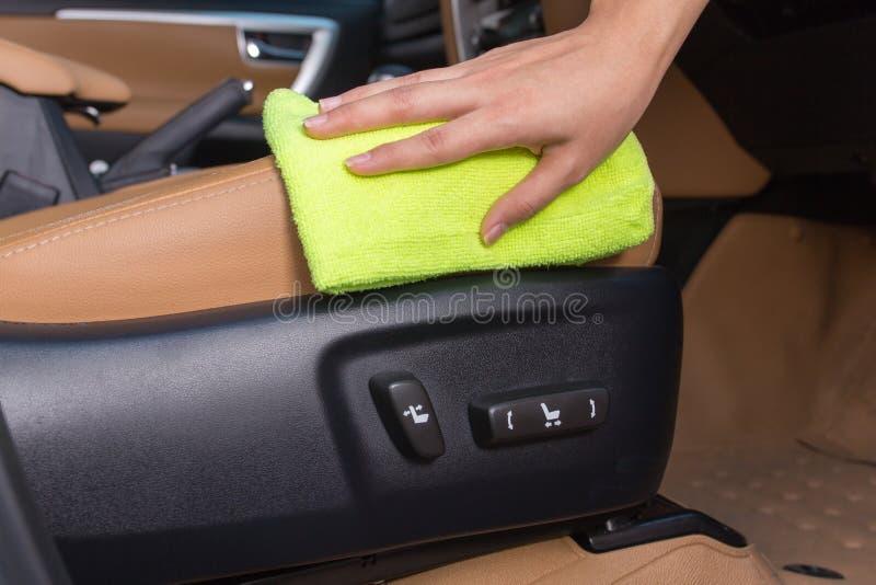 La main avec le nettoyage jaune de tissu de microfiber dans des séances de voiture élisent photo stock