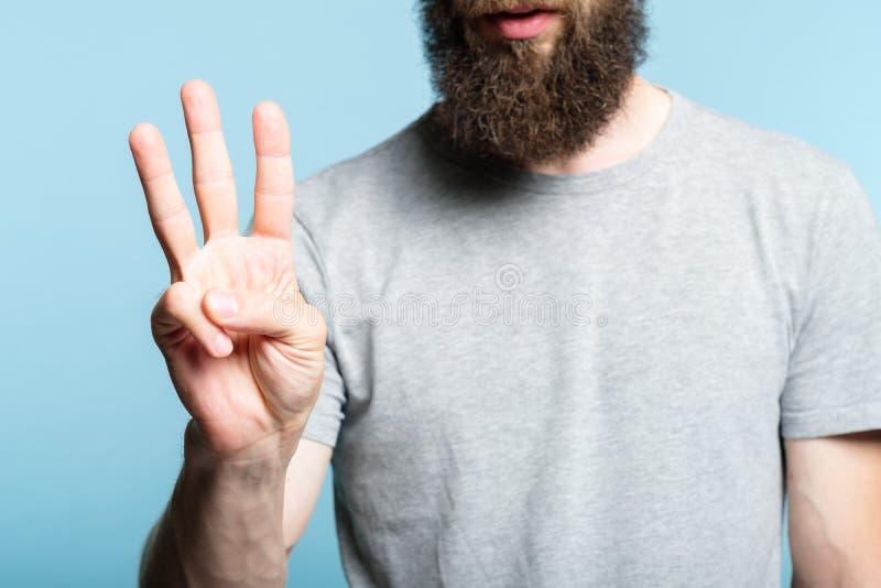 La main barbue le numéro trois d'exposition d'homme comptent le geste photos libres de droits